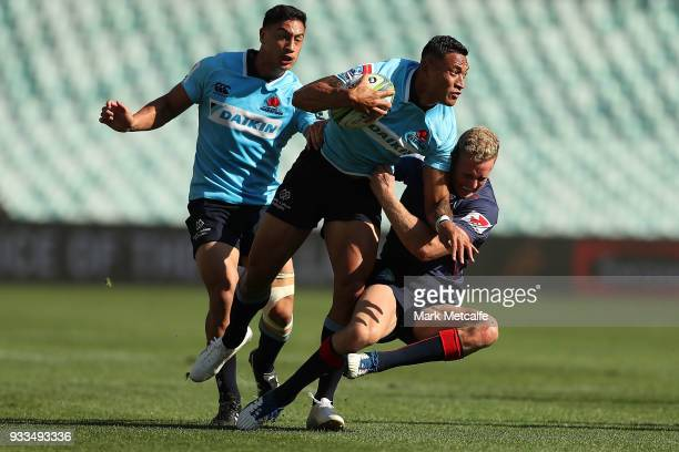 Israel Folau of the Waratahs is tackled by Reece Hodge of the Rebels during the round five Super Rugby match between the Waratahs and the Rebels at...
