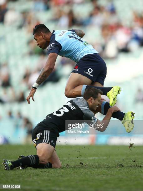 Israel Folau of the Waratahs is tackled by Tim Bateman of the Crusaders during the round six Super Rugby match between the Waratahs and the Crusaders...