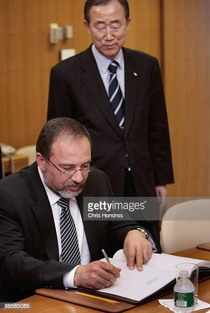 Israel foreign minister Avigdor Lieberman signs a guest book as UN Secretary General Ban Kimoon looks on before a meeting June 19 2009 at the United...