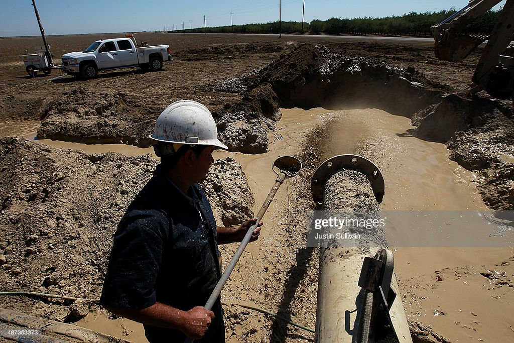 Israel Garcia with Arthur & Orum Well Drilling checks muddy water as it is discharged from a well drilling rig on April 29, 2014 near Mendota, California. As the California drought continues, Central California farmers are hiring well drillers to seek water underground for their crops after the U.S. Bureau of Reclamation stopped providing Central Valley farmers with any water from the federally run system of reservoirs and canals fed by mountain runoff.