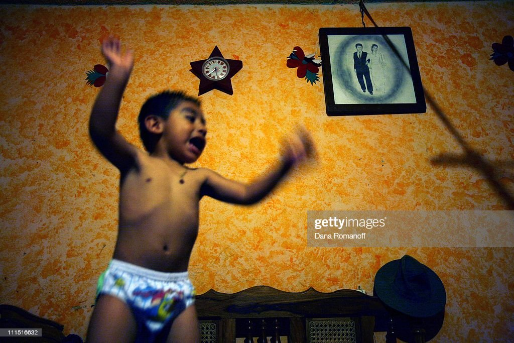 Israel Hernandez Tejeda, three, jumps on the bed that he shares with his mother and older brother. Behind him is a wedding photograph of his mother and father. Israel has never met his father who has been working in the U.S. for the past 20 years, returning home every couple of years for a few months at a time. Israel's two older brothers have also been in the U.S. for the past eight years and have never returned home. Israel's mother, Yolanda, says 'Many marriages don't make it. The women can't sustain, the men find others and don't send money. It's the children that pay. It's not their fault but they suffer.' Due to stricter and more risky border crossings, migrants living in the U.S. are not returning home to Mexico in fear they will not be able to get back across. Immigration is tearing apart families and changing the societal roles in rural Mexico.
