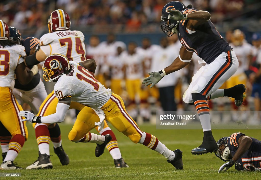 Israel Idonije #71 of the Chicago Bears leaps over teammate Major Wright #21 to chase down Robert Griffin III #10 of the Washington Redskins during a preseason game at Soldier Field on August 18, 2012 in Chicago, Illinois.
