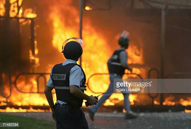 Israeli police officers run as a building burns following a Katyushastyle rocket slammed into the building in the northern coastal town oh Nahariya...