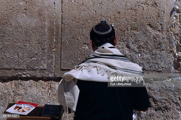 Israel, Jerusalem, A Jewish man wearing a traditional prayer shawl praying at the Western Wall.