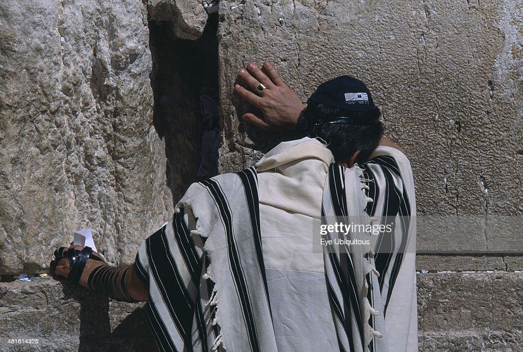 A Jewish man wearing a traditional prayer shawl praying at The Western Wall : News Photo