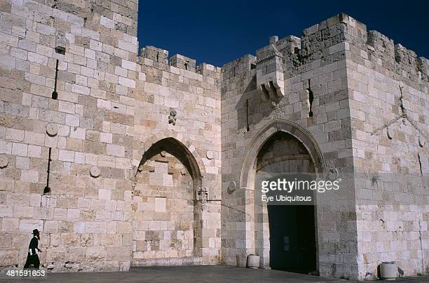 Israel Jerusalem The Jaffa Gate Orthodox Jewish man walking next to stone walls towards gate