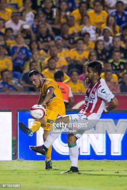 Israel Jimenez of Tigres kicks the ball over Daniel Alvarez of Necaxa during the 16th round match between Tigres UANL and Necaxa as part of the...