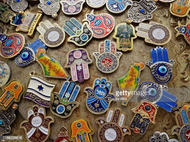 israel souvenir shopping, refrigerator magnets with hebrew, russian-cyrillic, latin scripts,souvenirs of a travel - hamsa symbol stock photos and pictures