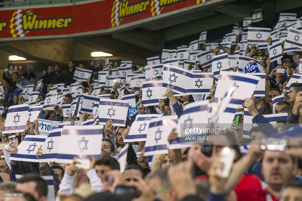 Israel supporters hold up posters with a picture of the national flag and cheer during their Euro 2016 Group B qualifying match against Bosnia-Herzegovina at the Sammy Ofer Stadium in the Israeli coastal city of Haifa on November 16, 2014.