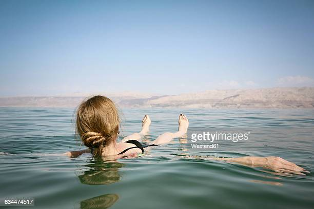 israel, woman floating on water of the dead sea - israeli woman stock pictures, royalty-free photos & images