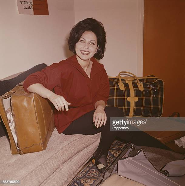 Israeli actress Haya Harareet pictured sitting on a couch surrounded by suitcases and luggage in 1962