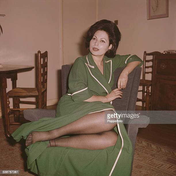 Israeli actress Haya Harareet pictured wearing a green gown in a living room in 1962