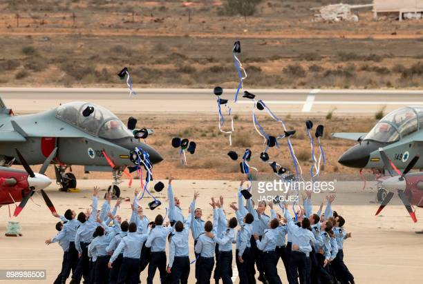 TOPSHOT Israeli Air Force pilots throw their hats in the air as they celebrate during their graduation ceremony at the Hatzerim Israeli Air Force...