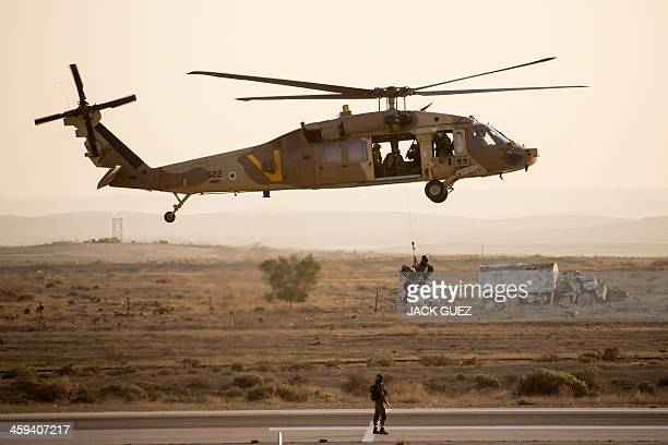 Israeli air force soldiers display their skills with an UH60 Black Hawk helicopter during an air show at the graduation ceremony of Israeli air force...