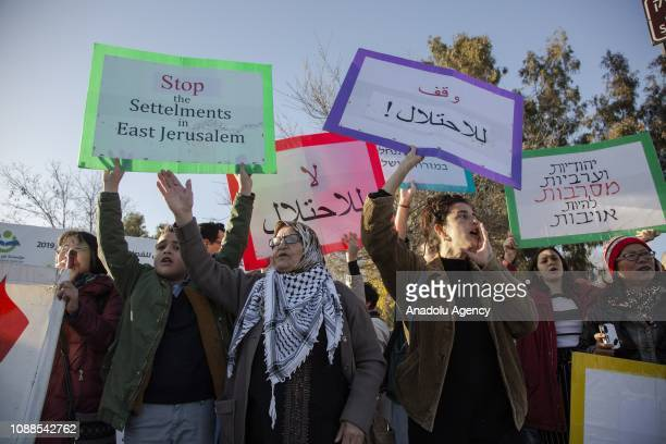 Israeli and foreigner peace activists hold banners during a protest against Israeli authorities' decision on evacuating Palestinian families who live...