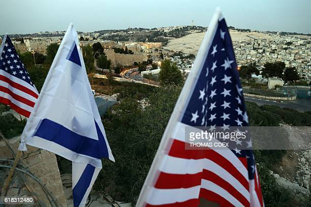 Israeli and US flags are flutter over the ramparts of Jerusalem's Old City as Israeli supporters of US republican presidential candidate Donald Trump...