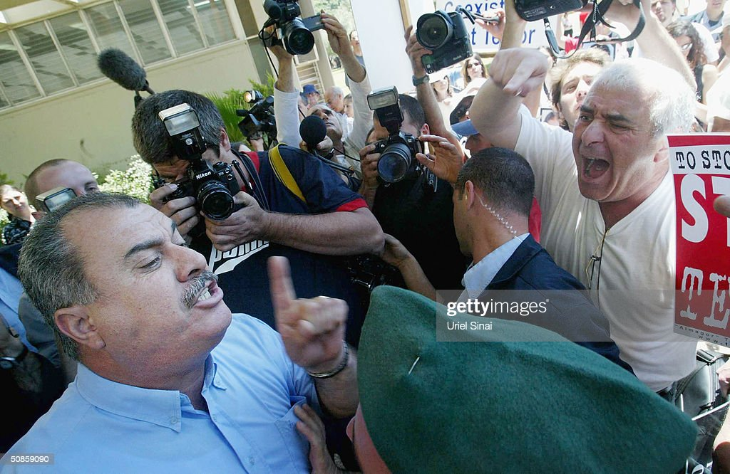 Israeli Arab Knesset member Muhammad Barke (L) argues with right wing Israelis, after the judicial ruling in the trial of Marwan Barghoutti, head of the Palestinian Fatah Tanzim and Al-Aqsa Martyrs' Brigades, outside the Tel Aviv District Court on May 20, 2004 in Tel Aviv, Israel. The court convicted Barghoutti of five counts of murder after Israel accused him of leading Palestinian militants in terror attacks against dozens of Israeli targets since the outbreak of the intifada.