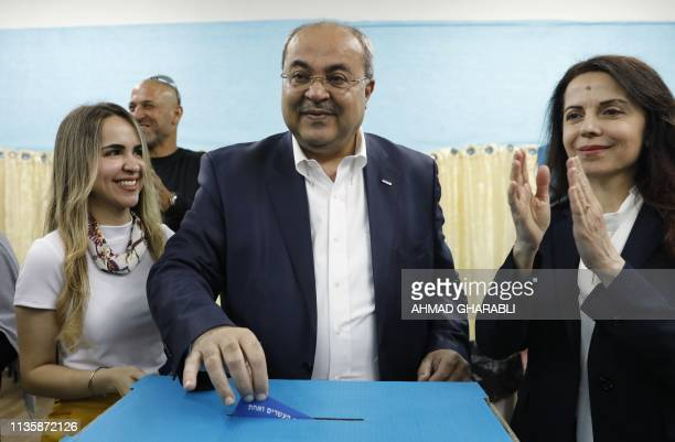 Israeli Arab politician Ahmed Tibi stands between his daughter and wife as he casts his vote during Israel's parliamentary elections on April 9 2019...
