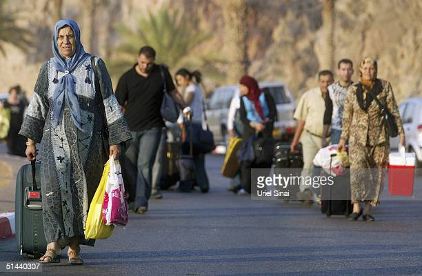 Israeli Arabs cross the border into the Israeli town of Eilat from the Egyptian resort of Taba on the Red Sea on October 8 2004 in Eilat Israel Some...