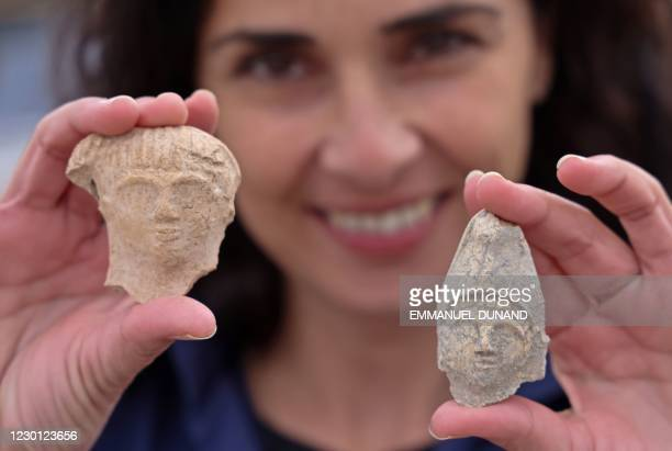 Israeli archaeologist Moran Balila holds figurines at the archaeological site where the largest oil lamp workshops was unearthed in the Israeli city...