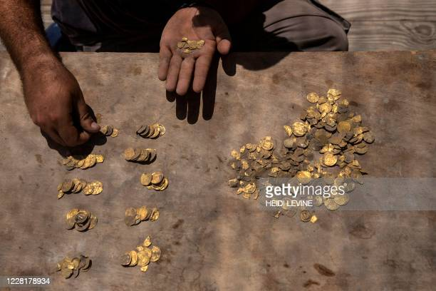Israeli archaeologist Shahar Krispin counts gold coins dating to the Abbasid Caliphate during a press presentation of the discovery at an...