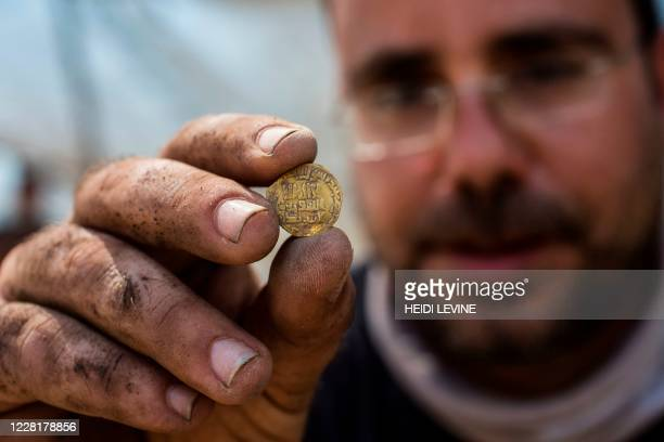 Israeli archaeologist Shahar Krispin displays a gold coin from a hoard dating to the Abbasid Caliphate during a press presentation of the discovery...