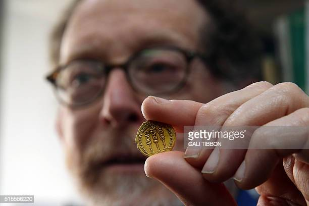 Israeli archeologist Donald T Ariel head curator of the coin department at the Israel Antiquities Authority holds up a 24 karat gold coin on March 14...