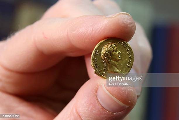 Israeli archeologist Donald T. Ariel, head curator of the coin department at the Israel Antiquities Authority holds up a 24 karat gold coin, on March...