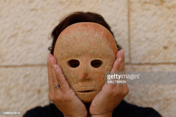 Israeli archeologist Ronit Lupu of the IAA Antiquities Theft Prevention Unit holds a rare stone mask dating to the Neolithic period which was found...