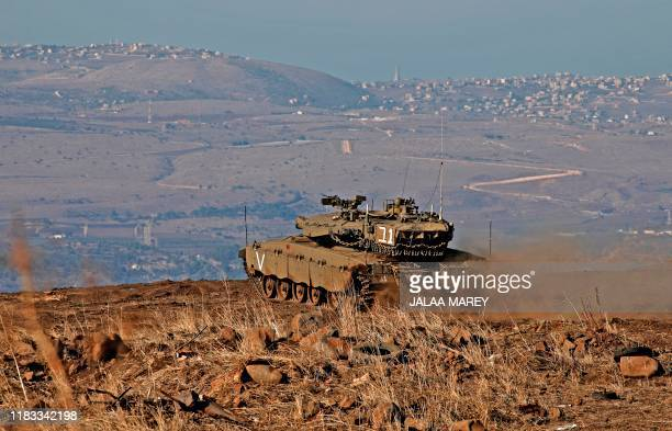 Israeli armoured vehicles are pictured on November 19, 2019 near the border with Syria in the annexed Golan Heights. - Israel's anti-missile defence...