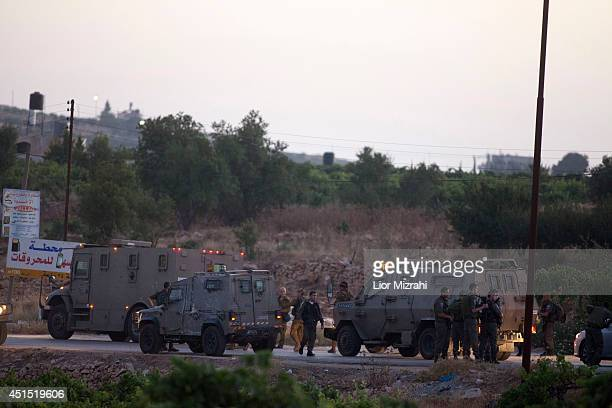 Israeli army and police stand by armoured vehicles on June 30 2014 in Halhoul north of Hebron West Bank The bodies of three Israeli teenagers who...