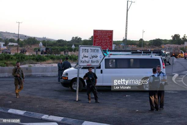 Israeli army and police stand gaurd on June 30 2014 at the enterence to Halhoul north of Hebron West Bank The bodies of three Israeli teenagers who...