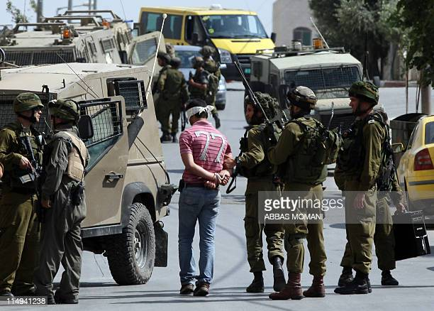 Israeli army forces arrest a man during a raid in the West Bank city of Ramallah on May 30 2011 Five Palestinians were arrest three from the village...