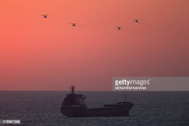 Israeli army helicopters fly over the Mediterranean sea at sunset near the Israeli port city of Ashdod on June 29 2015 Israel's navy halted a...