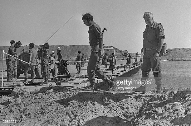 Israeli army MajorGeneral Ariel Sharon visits a bridge built by Israeli troops over the Suez Canal October 31 1973 in the Sinai Desert during the Yom...