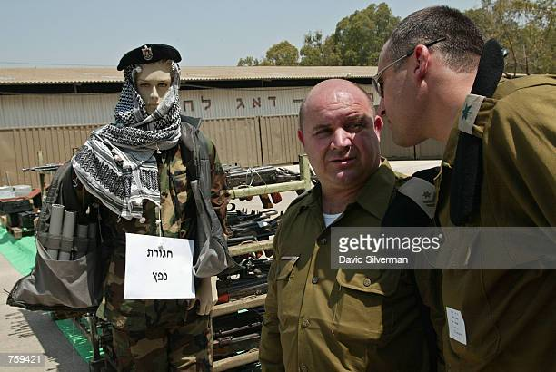 Israeli army officers whisper to each other as they stand next to a dummy dressed in Palestinian uniform and wearing a genuine suicide bomber's vest...