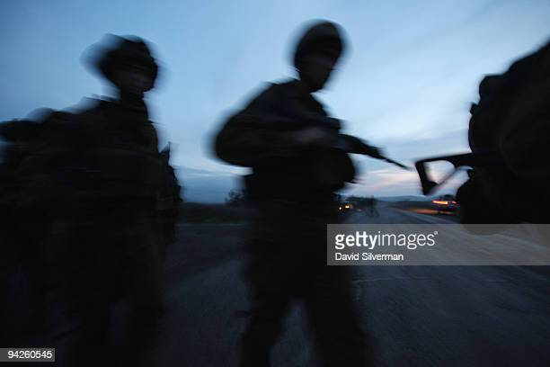 Israeli army paratroopers cross a road as they advance at daybreak during a livefire training exercise December 10 2009 on the Golan Heights The...