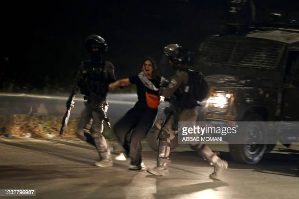Israeli army soldiers arrest a Palestinian woman during an anti-Israel protest over tension in Jerusalem, near the Jewish settlement of Beit El near...