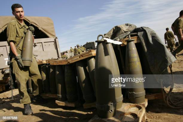 Israeli army soldiers prepare ammunition for their 155mm mobile artillery cannon after a night of action against Palestinian militants in the...