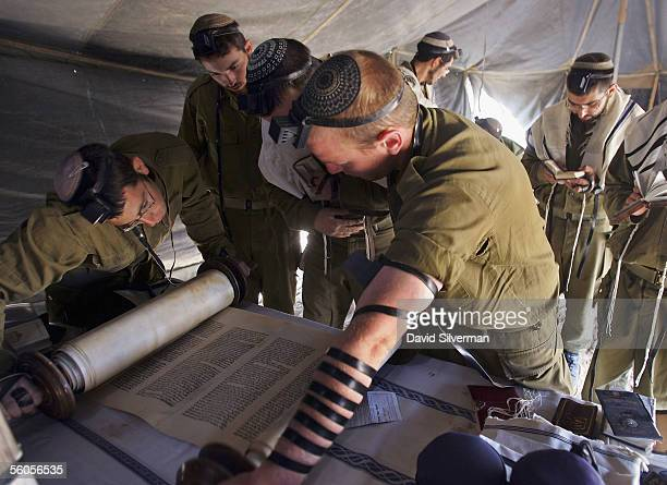 Israeli army soldiers read from a Jewish Torah scroll during their morning prayers in a tent near their 155mm mobile artillery cannon after a night...