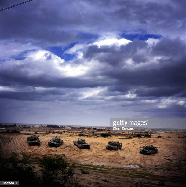 Israeli Army tanks sit deep in the sand dunes near the Kisofim route which is the only road leading into the Gush Katif settlement block November 15...
