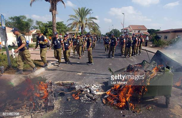Israeli army troops cross barricade on fire set by settlers in the Jewish settlement of Neve Dekalim part of the Gush Katif settlement bloc Gaza...