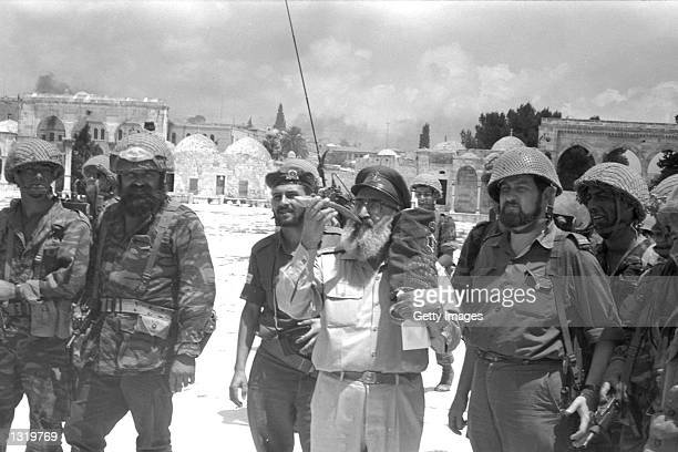 Israeli army''s Chief Rabbi Shlomo Goren carries a Torah scroll and blows a shofar June 71967 on the Temple Mount in Jerusalem Israel on the day of...