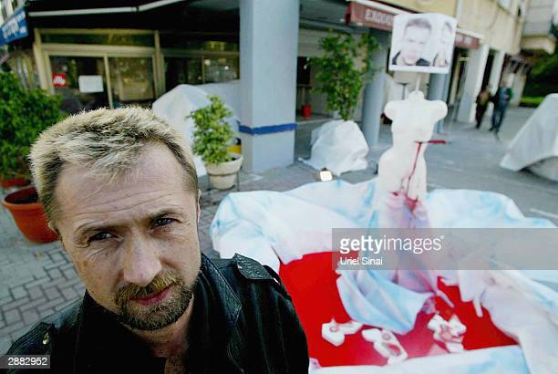 Israeli artist Pyotr Podovni is standing next to his artwork January 20 2004 in Tel Aviv Israel which includes a portrait of Mijailo Mijailovic the...