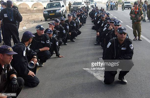 Israeli authorities kneel down in the main road in the settlement bloc of Gush Katif and near the front gate of the southern Gaza settlement of Neve...