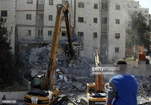 Israeli authorities use heavy machinery to demolish a house belonging to a Palestinian family that the authorities say was built without a...