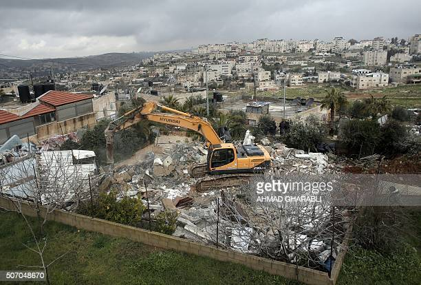 Israeli authorities use heavy machinery to demolish a house belonging to a Palestinian family that the authorities said was built without a...