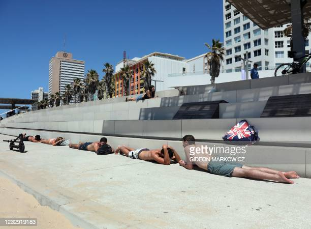 Israeli beachgoers take cover in the central city of Tel Aviv, on May 15 following the launching of rockets from the Gaza Strip controlled by the...