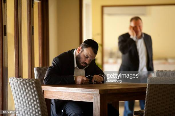 Israeli billionaire Dan Gertler left sits and checks messages on his smartphones at the Katanga Mining Ltd operating base while Pieter Deboutte chief...