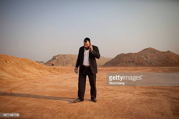 Israeli billionaire Dan Gertler talks on his smartphone while walking past mining rubble during a visit to Comide SPRL's Mashitu copper mine operated...